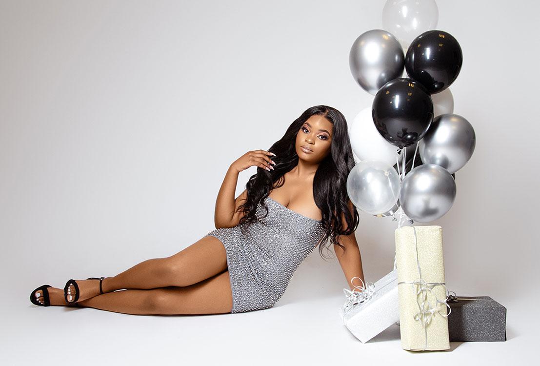 Donkere vrouw met ballonnen poseert op de grond verjaardag shoot